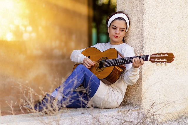 Girl Playing Guitar. Photo by Gavin Whitner. License: CC BY 2.0.